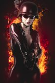 picture of latex woman  - Sexy brunette woman in latex jumpsuit with heavy gun and helmet over fire background - JPG