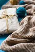 foto of blanket snow  - A gift to lie next to the coil bright filaments and blanket knitted on blue background - JPG