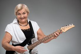stock photo of independent woman  - Grandma playing the guitar - JPG