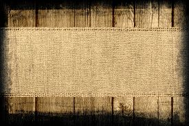 stock photo of canvas  - Burlap jute canvas banner textured with dark wood background - JPG