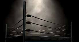image of boxing  - An old vintage boxing ring surrounded by ropes spotlit in the middle on an isolated dark background - JPG