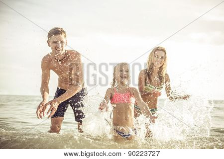 Playful Family Spraying Water And Having Fun