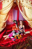 foto of harem  - Oriental beauty sit on cushions in her tent and holding a grape - JPG