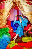 stock photo of harem  - Young oriental beauty sitting in a tent and holding on her head a dish with fruits - JPG