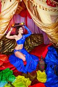 picture of harem  - Young oriental beauty sitting in a tent and holding on her head a dish with fruits - JPG
