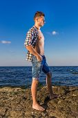 stock photo of nearly nude  - Attractive Young Fashion Sexy Man On Rock Near The Sea Water - JPG