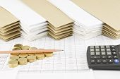 pic of piles  - Brown pencil on pile of gold coins as triangle with calculator on finance account have pile of paperwork with envelope as background - JPG