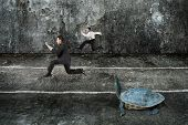 pic of tortoise  - Two businessmen running with turtle in the dark mottled concrete room - JPG