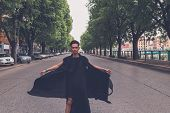 foto of tunic  - Young handsome Asian model dressed in black tunic posing in the city streets - JPG