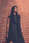 image of tunic  - Young handsome Asian model dressed in black tunic posing with a brick wall in background - JPG