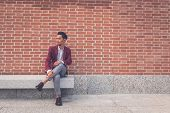 stock photo of blazer  - Young handsome Asian model dressed in red blazer sitting on a marble bench in the city streets - JPG