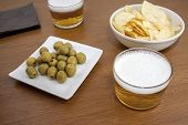 stock photo of crips  - two bears over a table with a typical Spanish tapa of olives and some crips - JPG