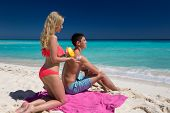 foto of sun tan lotion  - Woman applying heart shape sun protection lotion on man back summer tropical beach vacation - JPG