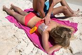 picture of sun tan lotion  - Man applying SPF sign with sun protection lotion on a woman back summer tropical beach vacation - JPG
