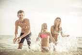 image of family vacations  - playful family spraying water and having fun - JPG