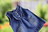 stock photo of habilis  - Fashion denim baby dress hanging on a hanger on a green background - JPG