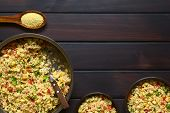 picture of sweet-corn  - Vegetarian couscous salad made with bell pepper tomato cucumber red onion and sweet corn kernels raw couscous on wooden spoon on the top - JPG