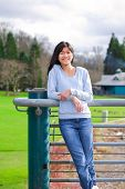 picture of biracial  - Young biracial teen girl standing leaning against railing at park - JPG