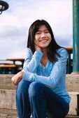 image of biracial  - Young biracial teen girl in blue shirt and jeans sitting on wooden steps outdoors on overcast cloudy day - JPG