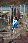 stock photo of biracial  - Young biracial teen girl in blue shirt and jeans sitting on large boulders along lake shore looking out over water - JPG