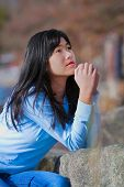 picture of biracial  - Young biracial teen girl in blue shirt and jeans quietly sitting outdoors leaning on rocks praying - JPG