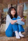 pic of biracial  - Sad biracial teen girl in blue shirt and jeans sitting on rocks along lake shore lonely expression - JPG