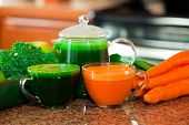 picture of kale  - Two cups of fresh vegetable juice on kitchen counter with vegetables in background. Raw carrots kale spinach cucumber apples.