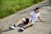 picture of knee-cap  - Handsome young man injured while running and jogging on road in the country in a sunny day - JPG