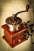 stock photo of wooden box from coffee mill  - Coffee bean grinder is on the burlap sack background - JPG