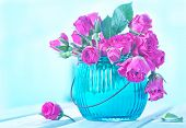 picture of bunch roses  - Bunch of small pink Roses in a glass vase over a wooden table - JPG