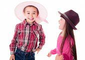 stock photo of opposites  - Happy boy and girl wearing opposite hats - JPG