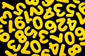 picture of zero  - Yellow numbers from one to nine including zero all single ditigits lie mixed in no spesific order on a black backgound - JPG