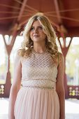 picture of evening gown  - Potrait of beautiful blond curly woman wearing evening peach color gown in outdoors. Fashionable and glamorous dress and style.