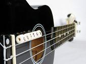 foto of ukulele  - Letters of beads on a black ukulele on a white background - JPG