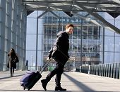 stock photo of carry-on luggage  - Portrait of a smiling young man walking with luggage at station - JPG