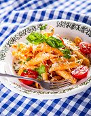 picture of pene  - Plate with pasta pene Bolognese sauce cherry tomatoes parsley top and basil leaves on checkered blue tablecloth - JPG