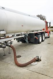 stock photo of tank truck  - Vertical shot of a fuel delivery truck pumping gas into gasoline container at station - JPG