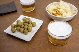 stock photo of crip  - two bears over a table with a typical Spanish tapa of olives and some crips - JPG