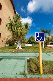 pic of handicapped  - Blue handicapped sign with wheelchair at tropical street - JPG