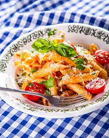 foto of pene  - Plate with pasta pene Bolognese sauce cherry tomatoes parsley top and basil leaves on checkered blue tablecloth - JPG