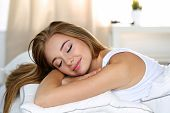 Young Beautiful Blonde Woman Portrait Lying In Bed poster