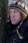 stock photo of ruddy-faced  - Portret of man in winter hat leaning on tree - JPG