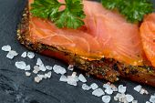 Постер, плакат: Smoked Salmon Slices And Seasoning On Natural Black Stone Background