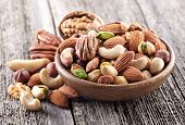 Nuts mix in a wooden plate poster