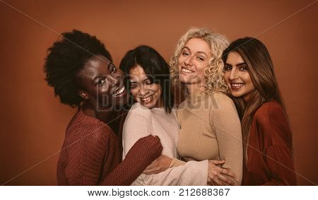 poster of Group of cheerful young women standing together on brown background. Multi ethnic female friends in studio.