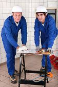 two skilled tradesman in blue jumpsuites watching a drawing poster