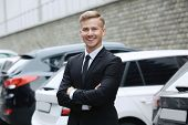 Young car salesman in formal suit near parked automobiles outdoors poster