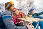 Family laughing and takes tea break during skiing on the mountain together poster