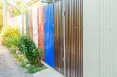 Colorful Fence Made Of Corrugated Metal Around A Suburban Area With A Gate And A Small Ornamental Gr poster