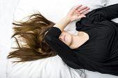Depressed young woman is lying in her bed, covering her eyes.Sorrow concept. poster
